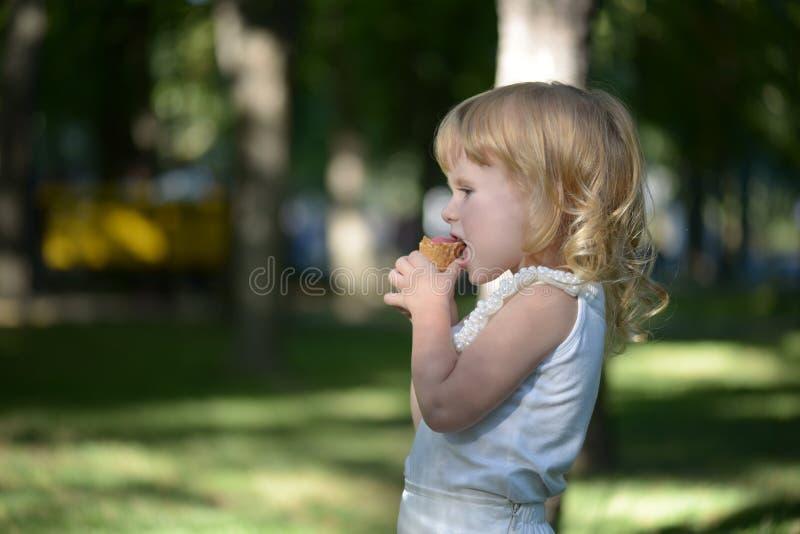Nettes kleines blondes Mädchen ist vor dem hintergrund hintergrundbeleuchtet lizenzfreie stockbilder