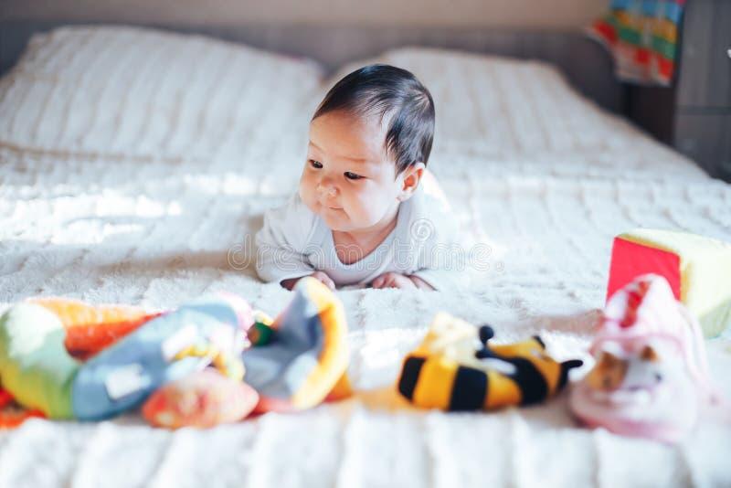 Nettes kleines dreimonatiges altes Baby, zu Hause spielend im Bett im Schlafzimmer, weiches Rücklicht vor ihr stockfotos