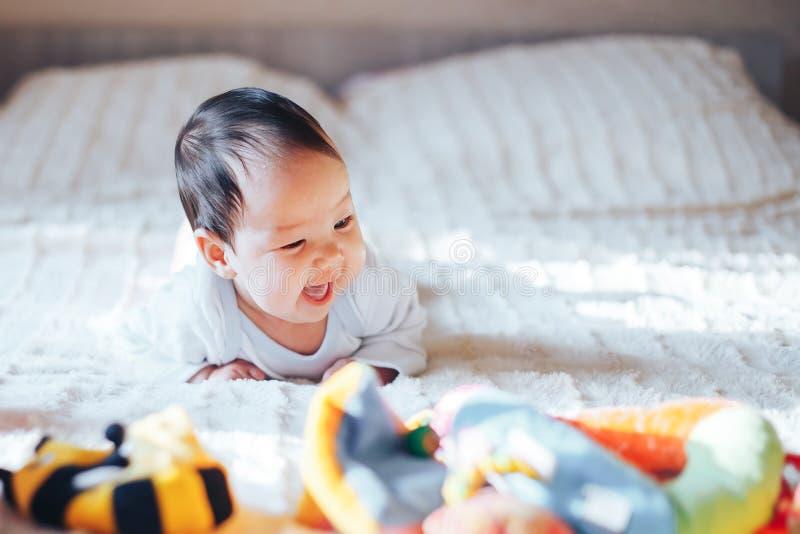 Nettes kleines dreimonatiges altes Baby, zu Hause spielend im Bett im Schlafzimmer, weiches Rücklicht vor ihr stockbilder