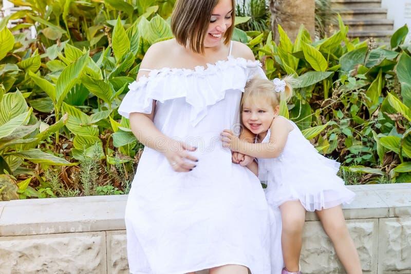 Nettes kleines emotionales blondy Kleinkindmädchen im Kleid, das ihren suring Weg schwangeren Mutter ` s Bauches im Park berührt  stockbild