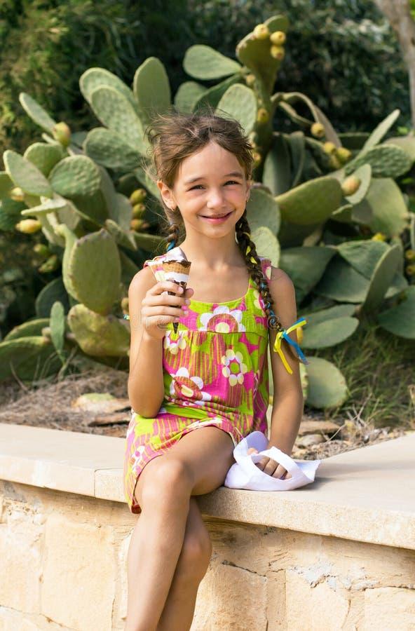 Nettes nettes kleines glückliches Mädchen, welches die Eisschillerlocke schmutzig auf Kaktushintergrund der Anlage isst stockfotos