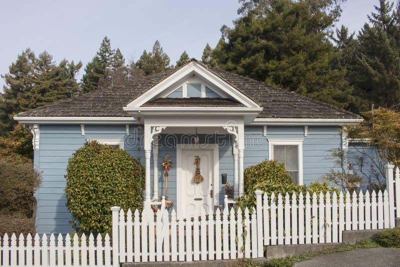 Nettes kleines Häuschen mit blauem Abstellgleise und victorian Noten- und hölzernerschindel- und weißerpalisadenzaun gegen hohe K lizenzfreie stockbilder