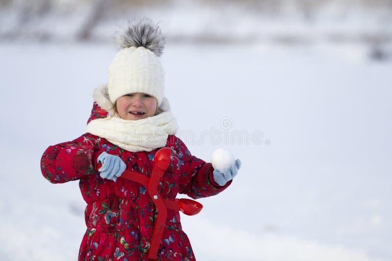 Nettes kleines junges lustiges zahnlos Kindermädchen in der warmen Kleidung, die den Spaß habend macht Schneebälle am kalten Tag  stockfoto