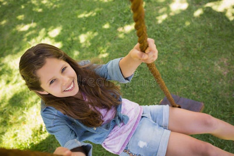 Nettes kleines junges Mädchen, das auf Schwingen sitzt stockfotos