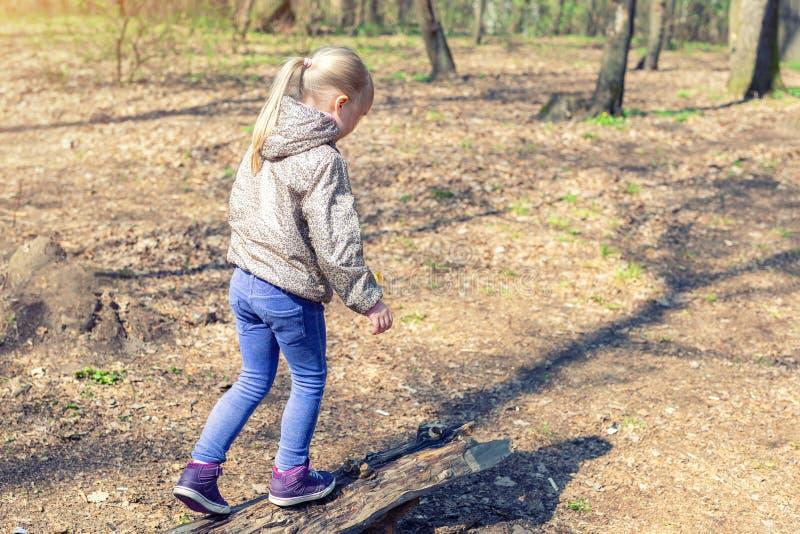 Nettes kleines kaukasisches blondes Mädchen, das auf hölzerner das LOGON-Waldentzückende Kind hat Spaß während des Wegs im Park i stockbild