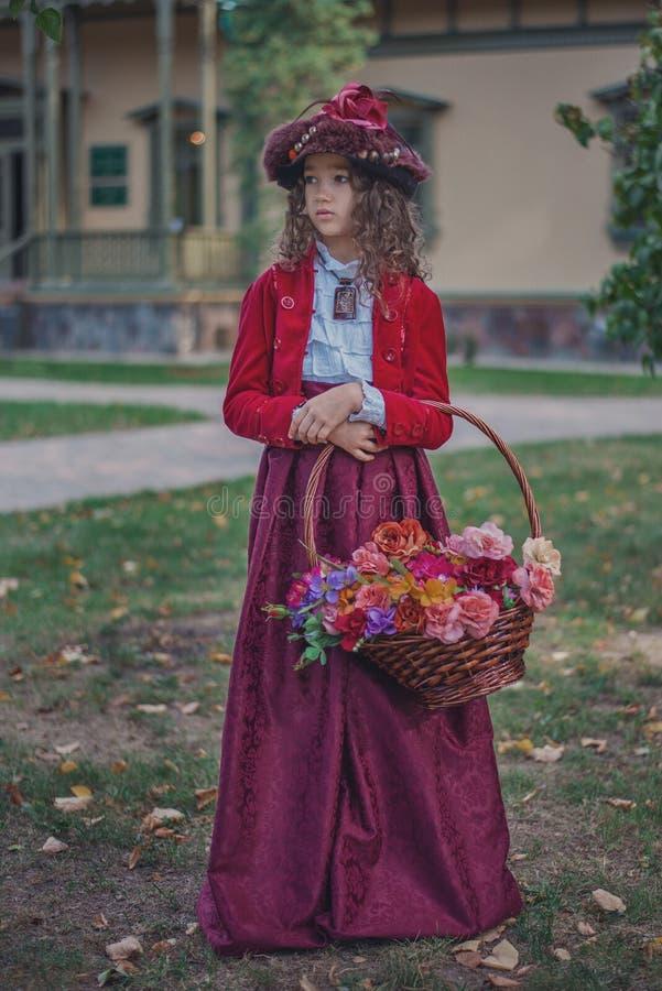 Nettes kleines kaukasisches Mädchen, das Retro- Kleidung trägt Nettes weibliches Kind im schönen Weinlesekleid stockbild