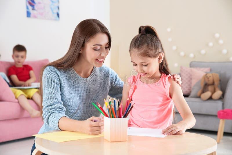Nettes kleines Kind, das bei Tisch mit junger Frau zeichnet stockfoto