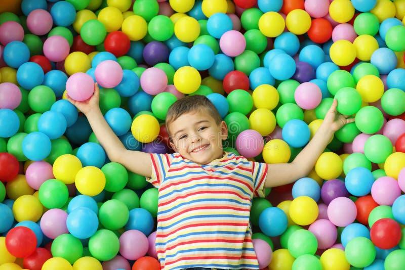 Nettes kleines Kind, das in der Ballgrube am Innenpark spielt stockfotografie