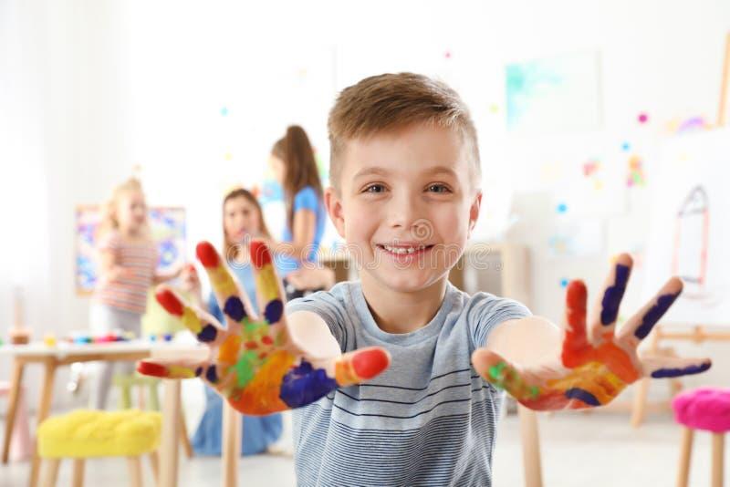 Nettes kleines Kind, das gemalte Hände an der Lektion zeigt lizenzfreies stockbild