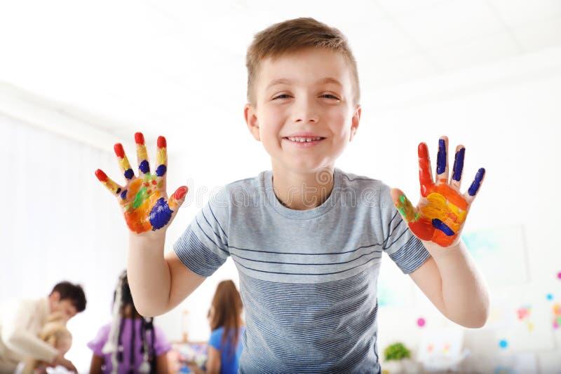 Nettes kleines Kind, das gemalte Hände an der Lektion zeigt lizenzfreie stockbilder