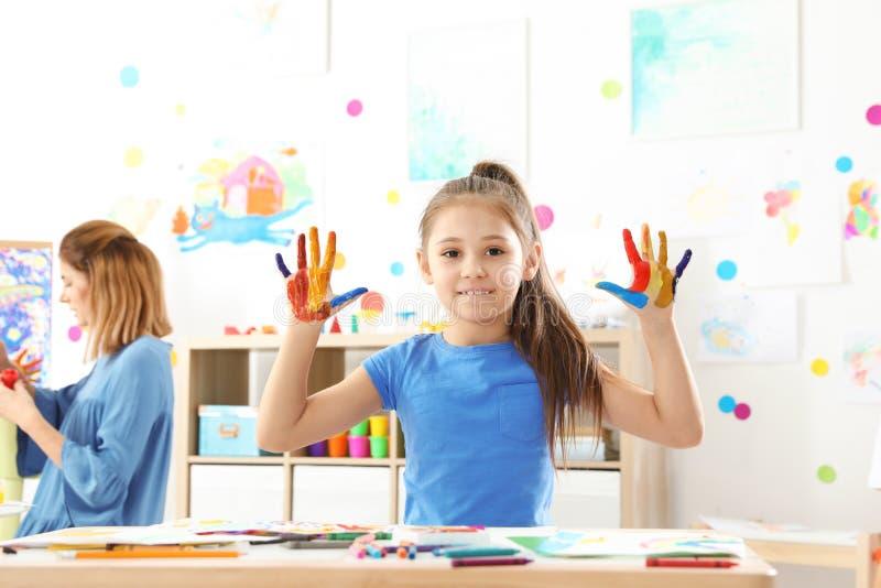 Nettes kleines Kind, das gemalte Hände an der Lektion zeigt lizenzfreie stockfotos