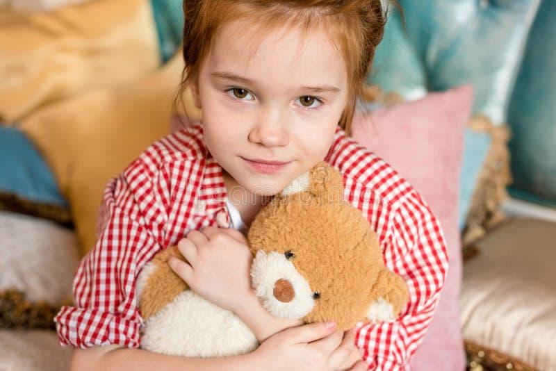 nettes kleines Kind, das Teddybären und das Lächeln umarmt stockfoto