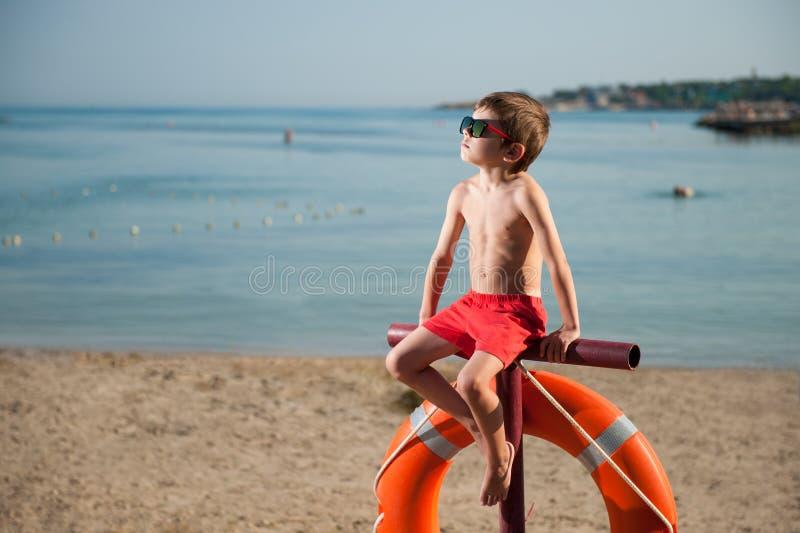 Nettes kleines Kind in der Sonnenbrille, die auf Strand mit Sommer des Rettungsrings im Freien sitzt lizenzfreie stockfotos