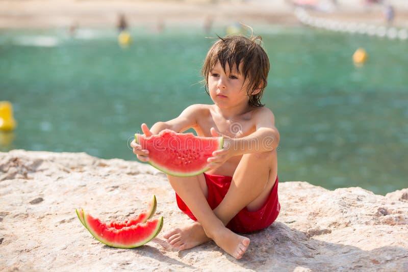 Nettes kleines Kind, Junge, Wassermelone auf dem Strand essend stockbild