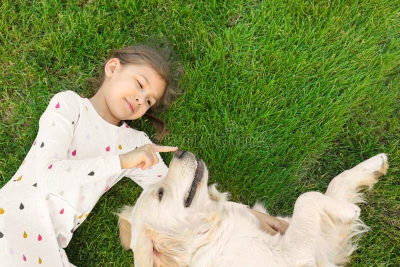 Nettes kleines Kind mit Haustier auf grünem Gras, Draufsicht lizenzfreie stockfotografie