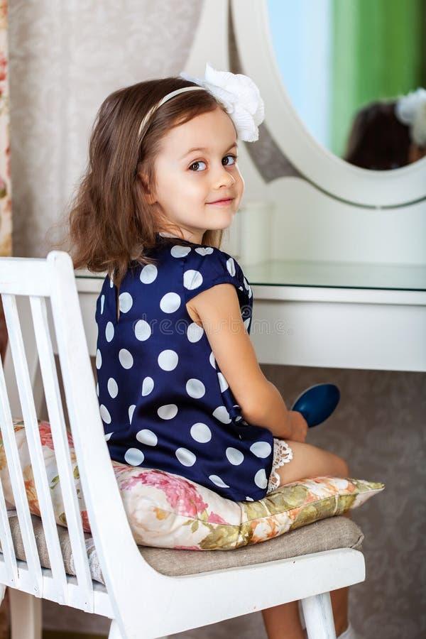 Nettes kleines Kindermädchen, das ihr Haar kämmt stockfoto