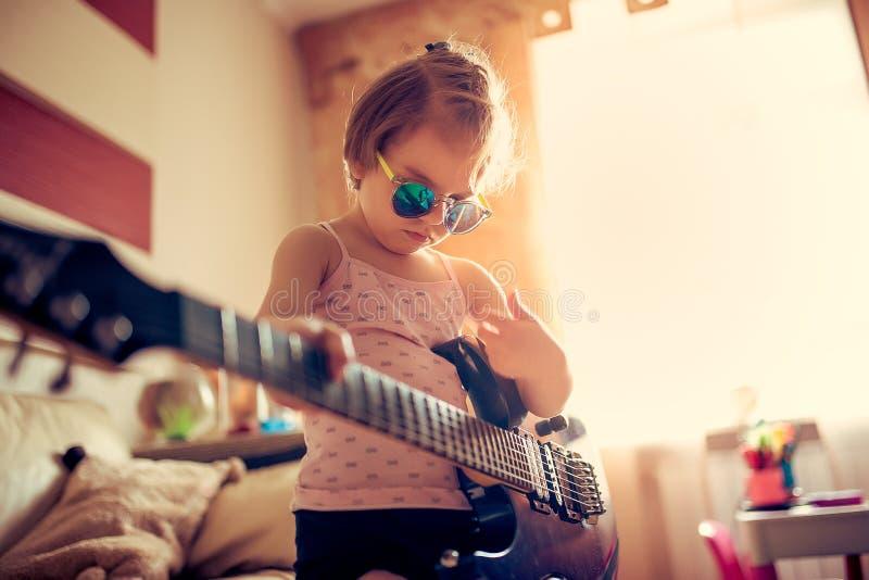 Nettes kleines Kindermädchen in der Sonnenbrille, die Gitarre spielt lizenzfreie stockfotografie