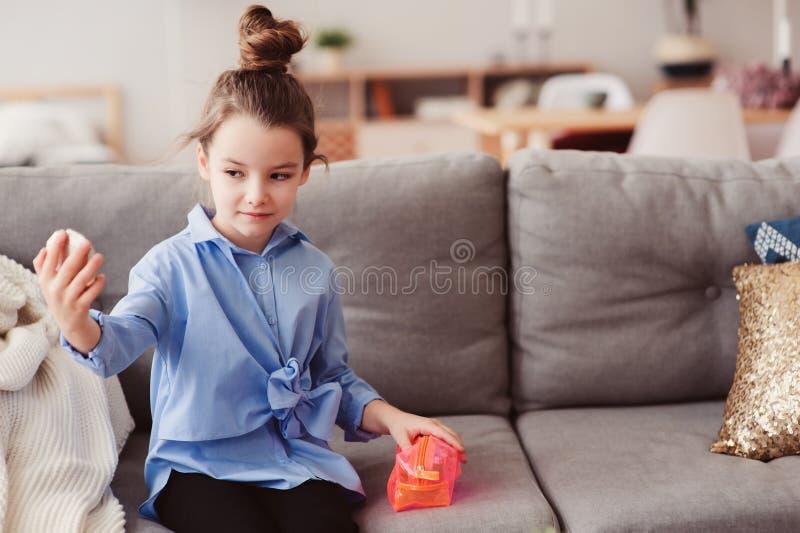 Nettes kleines Kindermädchen mit Spiegel und Kosmetiktasche Frisur zu Hause überprüfend lizenzfreies stockfoto