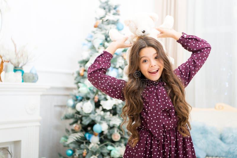 Nettes kleines Kindermädchen mit Weihnachtsgeschenk glückliches kleines Mädchen Winterurlaub feiern Rote Hintergrundnahaufnahme F stockfoto