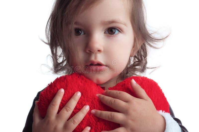 Nettes kleines Kindermädchenporträt, das rotes Herzspielzeug auf weißem b hält stockfotografie