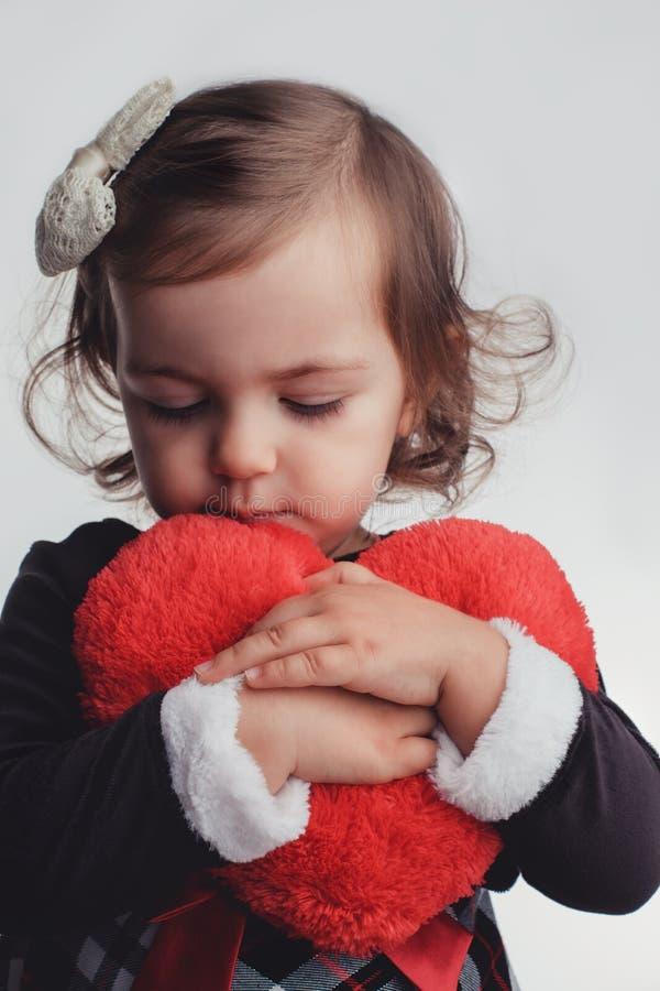 Nettes kleines Kindermädchenporträt, das rotes Herzspielzeug auf weißem b hält stockfoto