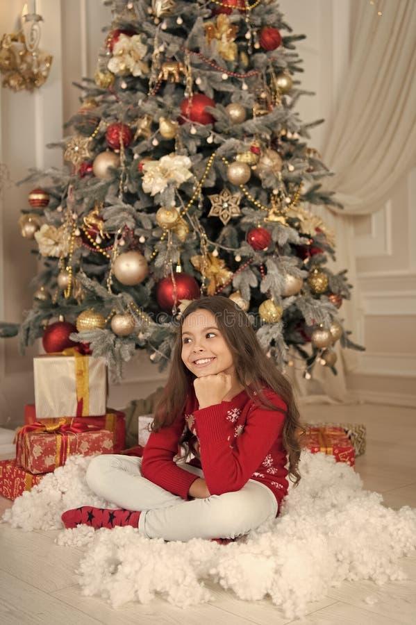 Nettes kleines Kinderm?dchen mit Weihnachtsgeschenk Ziehen des Weihnachtsbaums Weihnachten Weihnachtsfamilienurlaub Gl?ckliches n lizenzfreie stockfotos