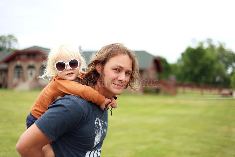 Nettes kleines Kleinkind-Mädchen, das Piggyback Fahrt von hübschem L erhält lizenzfreie stockbilder