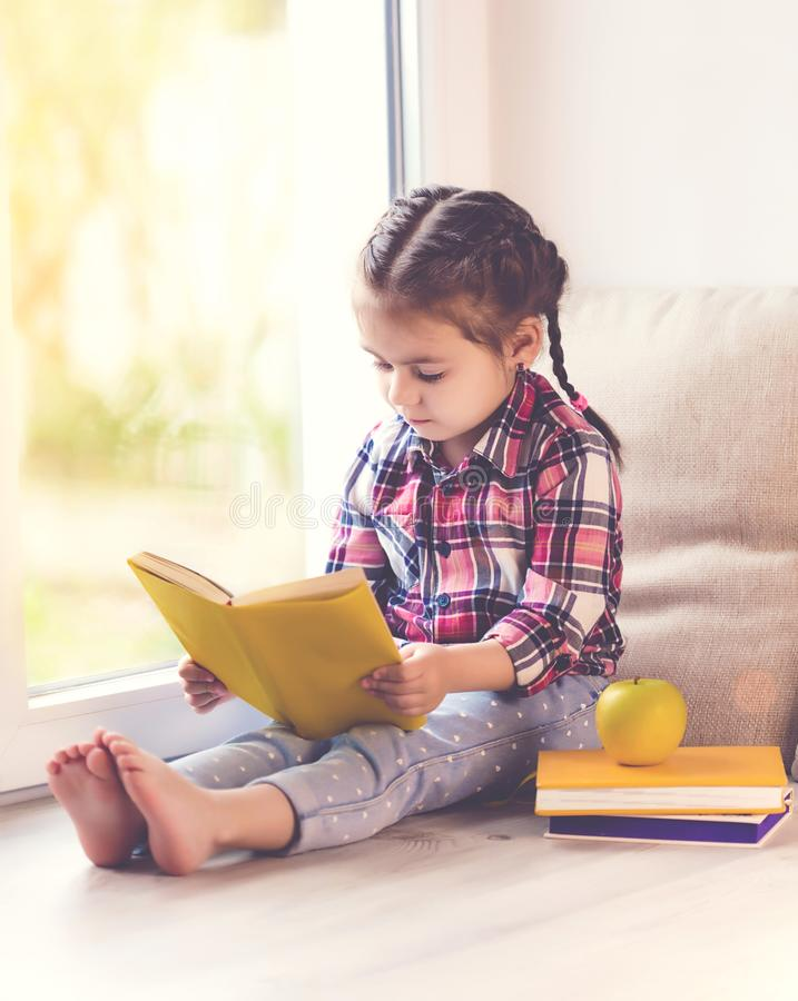Nettes kleines Kleinkindmädchen-Lesebuch, das am Fenster sonnigen Frühlingstag sitzt stockfoto