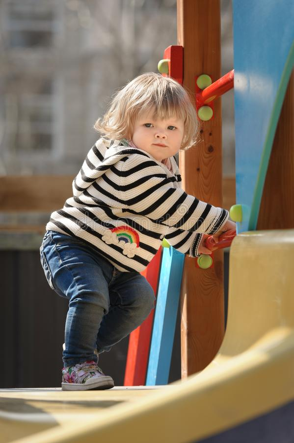 Nettes kleines Kleinkindmädchen, welches fast unten das Dia der Kinder schiebt stockfoto