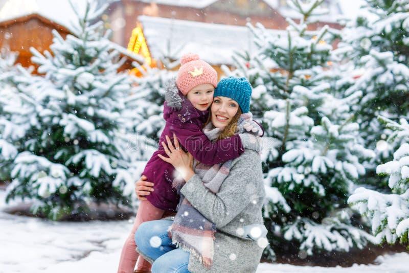 Nettes kleines lächelndes Kindermädchen und -mutter auf Weihnachtsbaummarkt Glückliches Kind, Tochter und junge Frau im Winter stockfoto