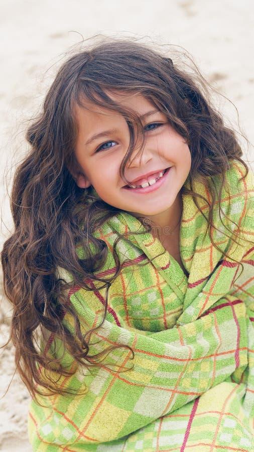 Nettes kleines lateinisches lächelndes Mädchen am Strand bedeckt mit dem grünen Tuch, das die Kamera untersucht lizenzfreies stockbild