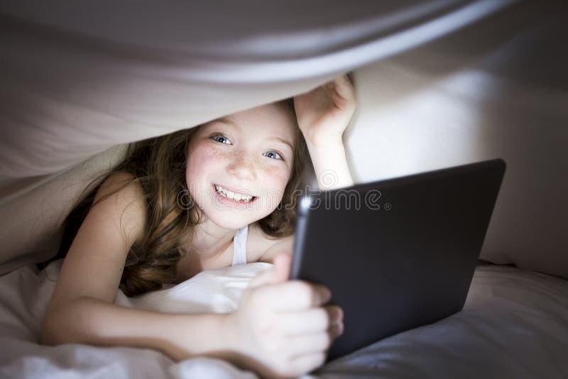 Nettes kleines Mädchen allein mit Tablet-Computer unter Decke nachts in einer Dunkelkammer lizenzfreie stockfotografie
