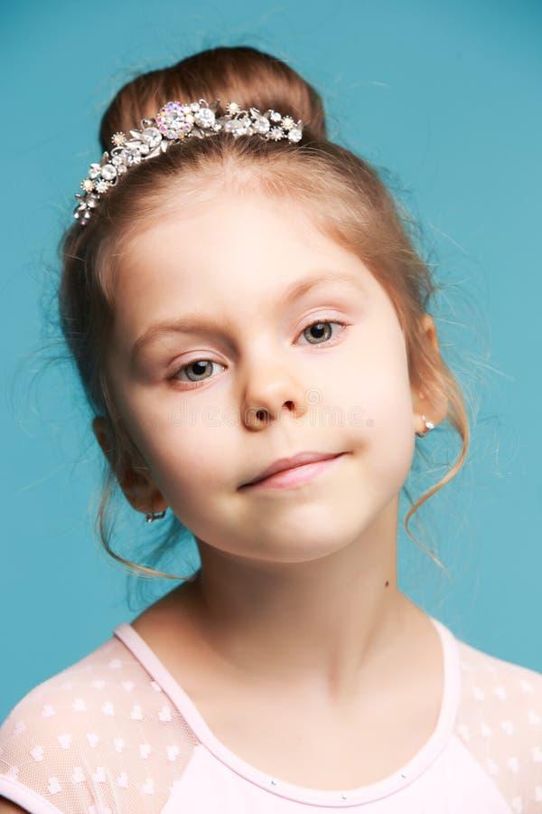 Nettes kleines Mädchen auf einer blauen Hintergrundnahaufnahme stockfotografie