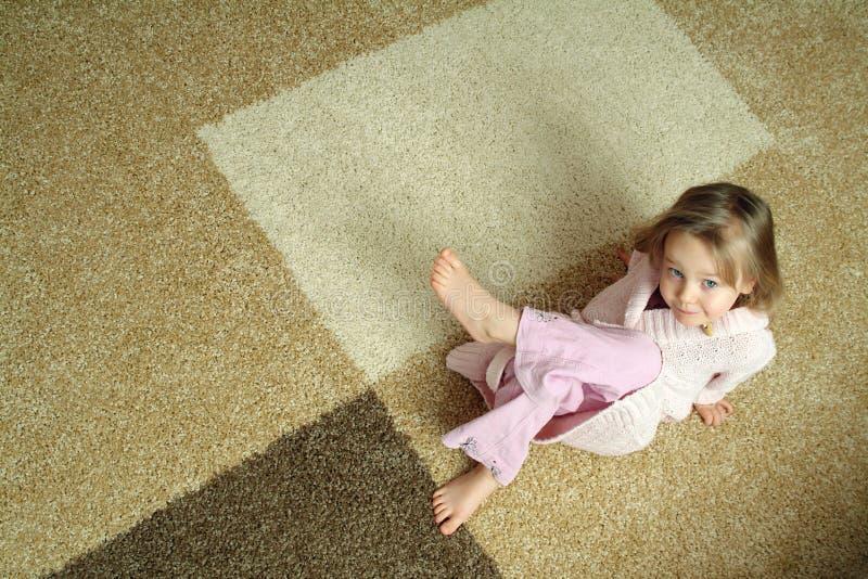 Nettes kleines Mädchen auf Teppich stockfotografie