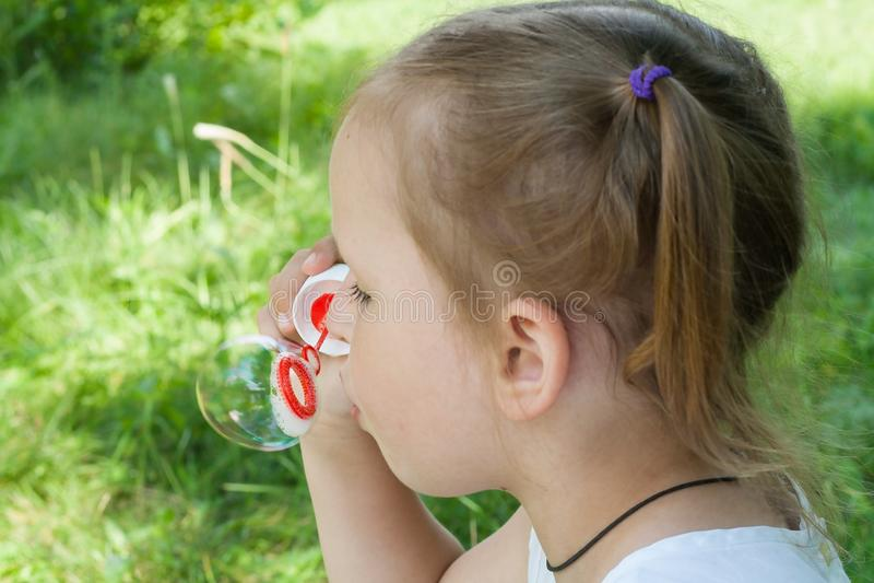 Nettes kleines Mädchen bläst eine große Blase auf stockfoto