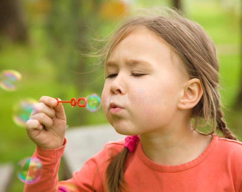 Nettes kleines Mädchen brennt Seifenluftblasen durch lizenzfreies stockfoto