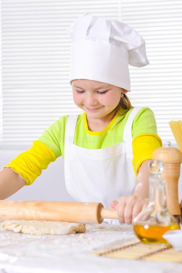 Nettes kleines Mädchen Chef ` s im Hut-Backenkuchen in der Küche stockfoto