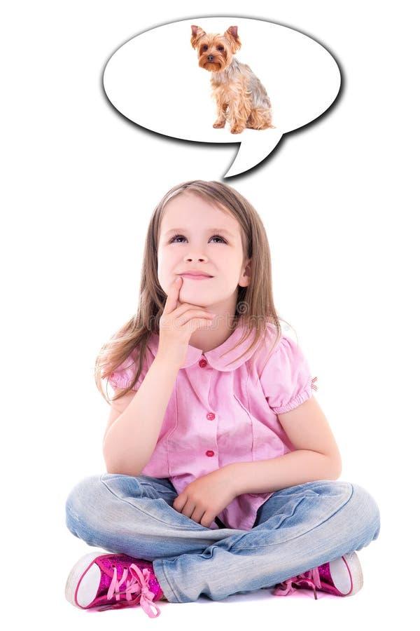 Nettes kleines Mädchen, das über den Hund lokalisiert auf Whit sitzt und träumt stockfoto