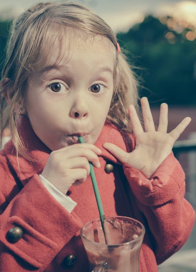 Nettes kleines Mädchen, das als Trinken der heißen Schokolade auf Stroh wellenartig bewegt stockbilder