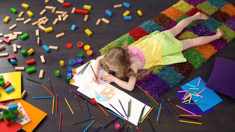 Nettes kleines Mädchen, das auf Boden liegt und mit Farbbleistiften auf Papier, Kunst zeichnet stockfoto