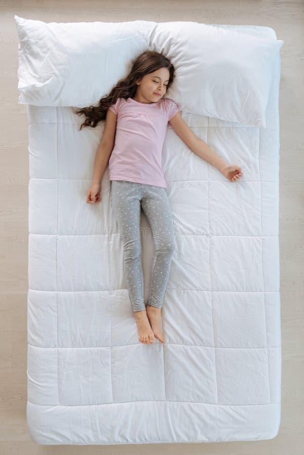 Nettes kleines Mädchen, das auf dem Bett schläft stockfotos