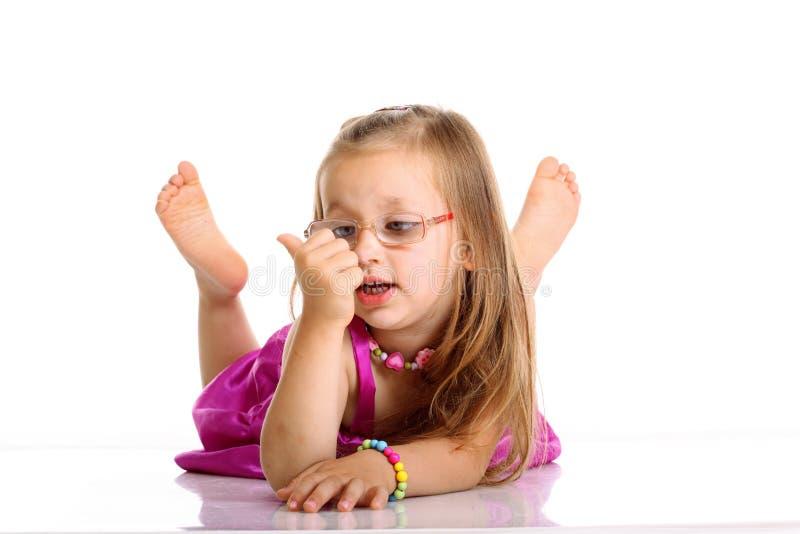 Nettes kleines Mädchen, das auf dem Boden lokalisiert liegt stockbilder