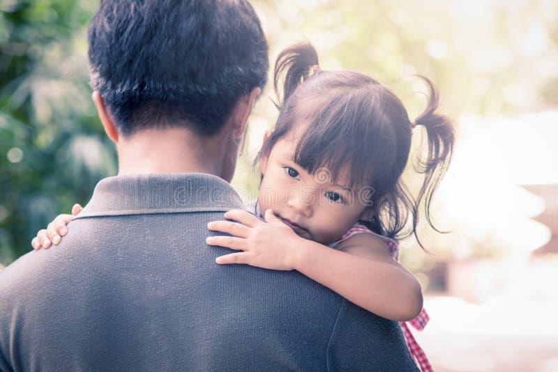 Nettes kleines Mädchen, das auf der Schulter ihres Vaters stillsteht stockbild
