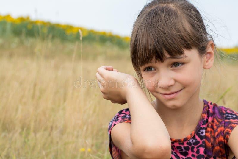 Nettes kleines Mädchen, das auf einem Gebiet lächelt lizenzfreie stockbilder