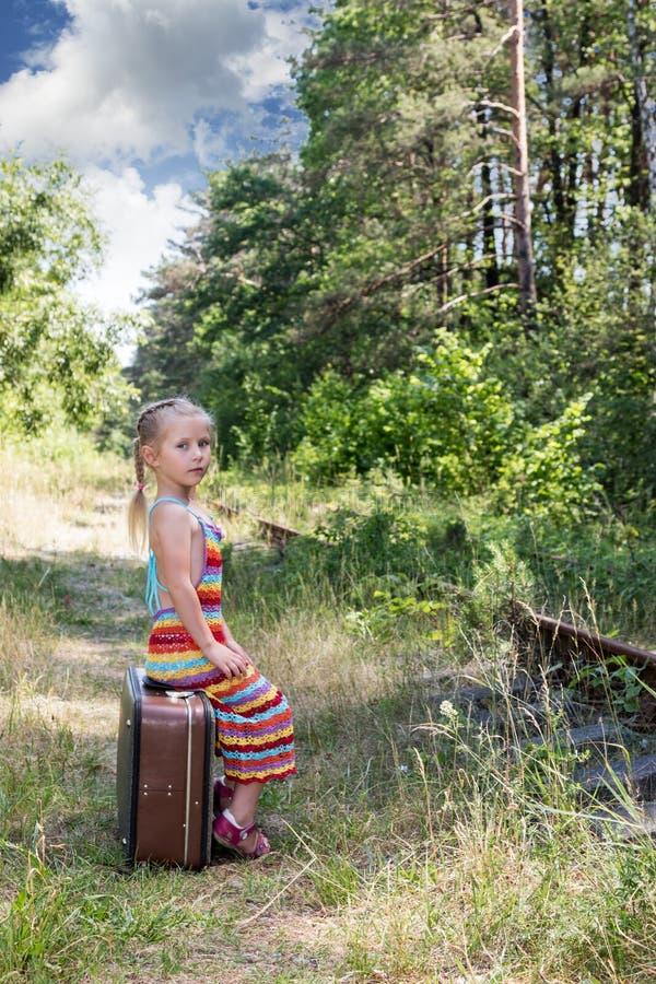Nettes kleines Mädchen, das auf einem großen Koffer sitzt lizenzfreies stockbild
