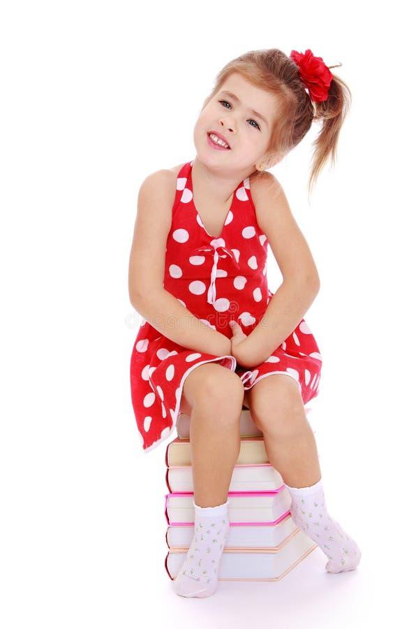 Nettes kleines Mädchen, das auf einem Stapel von Büchern sitzt lizenzfreie stockbilder