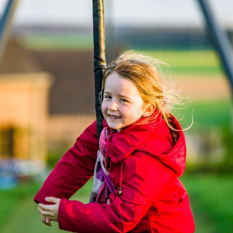 Nettes kleines Mädchen, das auf Kinderspielplatz spielt stockfotografie