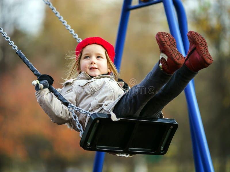 Nettes kleines Mädchen, das auf ständigem Schwanken schwingt lizenzfreie stockbilder