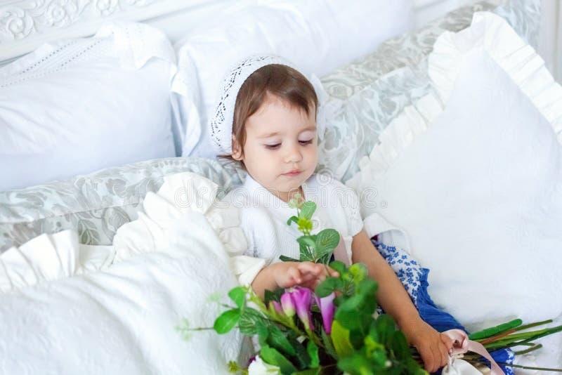 Nettes kleines Mädchen, das auf weißes Bett springt stockbild