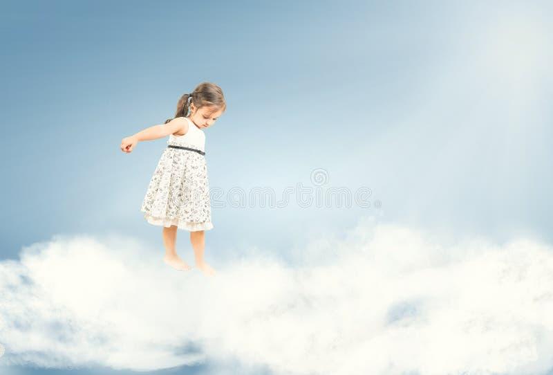Nettes kleines Mädchen, das barfuß auf Wolken steht stockbild
